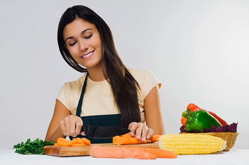 Close-up of a woman cutting vegetables --- Image by © Glowimages/Corbis